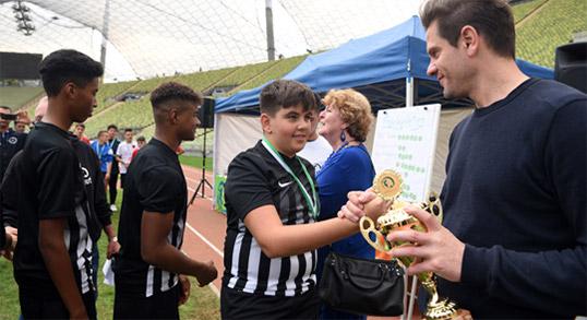 Michael Gurksi übergibt Pokal an einen jungen buntkicktgut-Fussballspieler